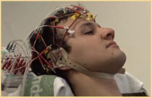 Person som gör en EEG-undersökning (elektroencefalografi), han har en hjälm med en massa sladdar fastsatta på huvud och panna.
