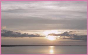 Soluppgång över ett vattendrag, man ser horisonten och moln på himlen framför solen.