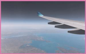 Foto taget genom fönstret på ett flygplan, man ser ena vingen och landskapet nedanför.