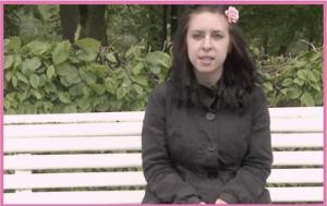 Jessica sitter på en parkbänk vid en skog, hon har svart jacka och en rosa ros i sitt svarta hår.